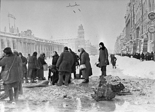 תושבי לנינגרד הנצורה אוספים מי שתייה משלולית מים שנקוו בחור באספלט בשדרות נבסקי לאחר הפצצה ארטילרית, דצמבר 1941 (צילום: בוריס פ. קודויארוב)