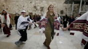 """אשה לבושה מדי צבא וטלית רוקדת יחד עם חברות ארגון """"נשות הכותל"""" סמוך לכותל המערבי בעיר העתיקה בירושלים, 3.3.14 (צילום: מרים אלסטר)"""