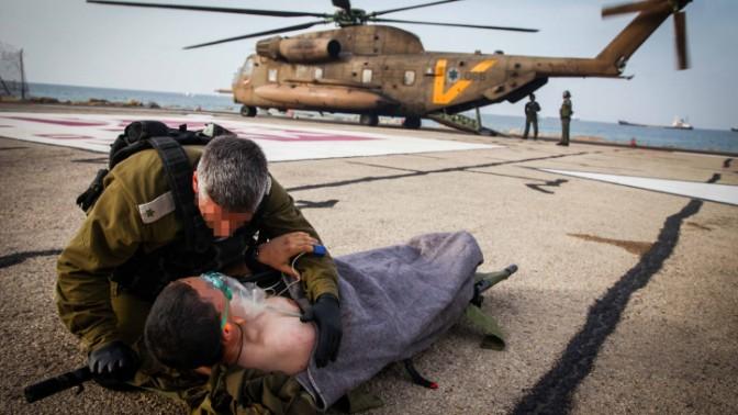 """קצין צה""""ל משוחח עם פצוע, 18.3.14 (צילום: אבישג שאר-ישוב)"""