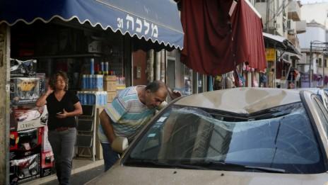 ישראלי מביט על רכב שנפגע מרסיס רקטה שיורטה מעל תל-אביב, 10.7.14 (צילום: מרים אלסטר)