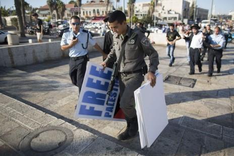שוטרים מחרימים שלטים בהפגנה בירושלים. מאחור: מפגין, איש נטורי-קרתא, נלקח לחקירה. 27.7.14 (צילום: יונתן זינדל)