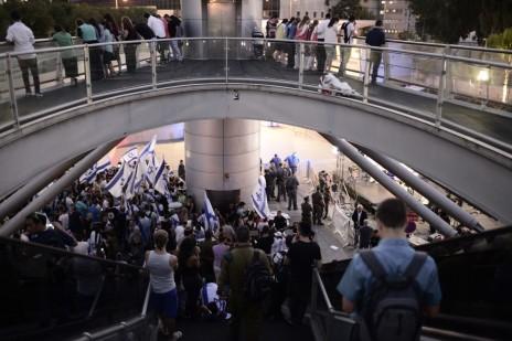 מפגיני ימין מתגודדים מחוץ לבסיס הקריה בתל-אביב. שוטרים חוצצים בינם ובין אולפן חדשות ערוץ 2. 29.7.14 (צילום: תומר נויברג)