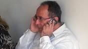 """הפרשן הכלכלי הבכיר של """"מעריב"""", יהודה שרוני, משתמש בטלפון סלולרי (צילום: """"העין השביעית"""")"""
