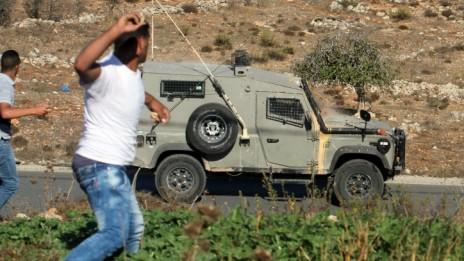 """פלסטינים מיידים אבנים לעבר רכב צה""""ל ליד הכניסה לבית-אל, 24.10.14 (צילום: STR)"""