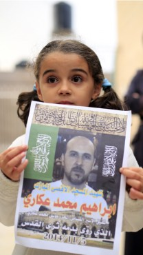 בת משפחתו של המחבל מחזיקה כרזה לזכרו, 5.11.14 (צילום: סלימאן ח'אדר)