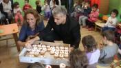 """יו""""ר יש עתיד יאיר לפיד מחלק סופגניות בגן ילדים, אתמול. 16.12.14 (צילום: פלאש90)"""