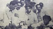 """היום הראשון של """"דבר"""", בדפוס """"הפועל הצעיר"""", תצלום שהופיע בעיתון בגיליון לרגל 25 שנות """"דבר"""". ליד השולחן עומדים (מימין): זלמן רובשוב (שזר), ברל כצנלסון, משה שרתוק (שרת) ומנדל קרופניק (קרוא) מנהל העיתון (צילום: י. בורודובסקי)"""