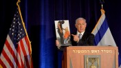 """ראש ממשלת ישראל, בנימין נתניהו, מציג תצלום שבו נראה פלסטיני חמוש מרצועת עזה בסצנה המזכירה את ההוצאות להורג של ארגון דאע""""ש (צילום: אבי אוחיון, לע""""מ)"""