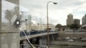 חלון מנוקב מכדור בזירת פיגוע דקירה ליד הקריה בתל-אביב, 8.10.15 (צילום: תומר ניוברג)