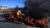 נער פלסטיני מג'ילזון עורם צמיגים בוערים על כביש סמוך לבית-אל, 24.11.14 (צילום: STR/פלאש 90)