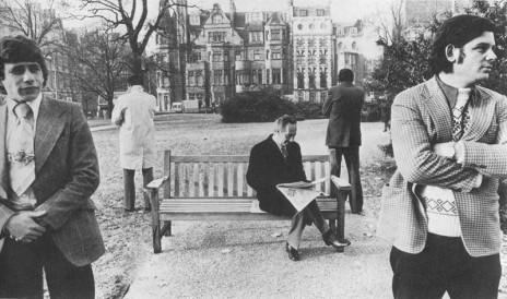 """תמונה 2: צילום מבוים של סאלי סואמס שהתפרסם בעמוד השער של ה""""סנדיי טיימס"""". שר הביטחון שמעון פרס קורא עיתון על ספסל בין מאבטחים בגן ציבורי ליד מלונו בלונדון, בשנות השבעים. """"חששתי שיקרה לו משהו ושיאשימו אותי"""", אמרה הצלמת, שהצילום מוצג כאן באדיבותה"""