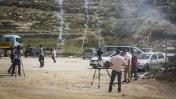 עיתונאים פלשתינים בהפגנה ליד כלא עופר למען שחרורו של העיתונאי עומאר נזאל, נמלטים מרימוני גז שנורו בידי כוחות ישראלים. 26.4.16 (צילום: פלאש90)