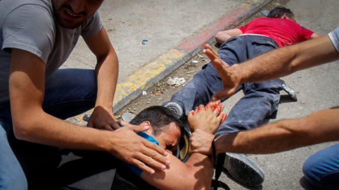 צלם פלסטיני פצוע שוכב ליד גופת פלסטיני שנורה על ידי ישראלי שרכבו נרגם באבנים, חווארה, 18.5.17 (צילום: נאסר אישתייה)